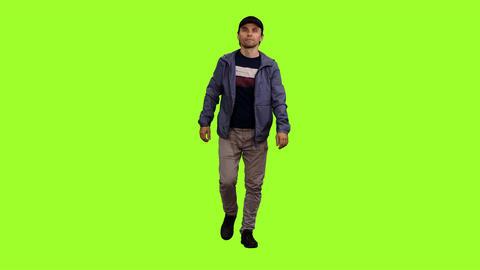 Walking man in black peaked cap on green screen background, Chroma key Footage