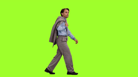 Businessman with suit jacket in hand walks on green background, Chroma key Footage