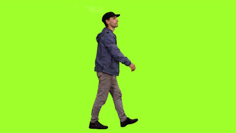 Side view of a walking man in black peaked cap on green screen background Footage