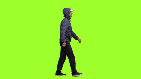 Hooded man walks on green screen background, Chroma key Live Action