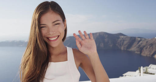 Pretty young lady waving Hello smiling looking at camera in Santorini Footage