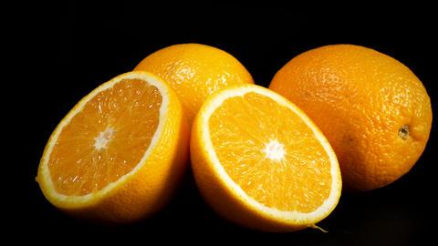 Slices of orange spinning against black background Filmmaterial