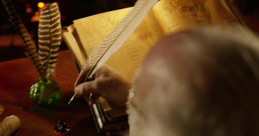 Santa Claus makes final adjustments to his list with a quill pen Footage