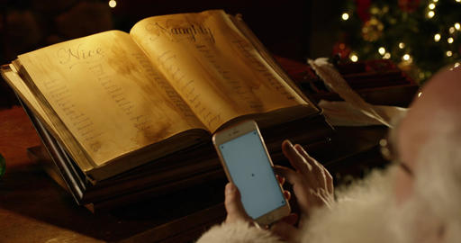Santa plays with smartphone. Naughty and Nice list sit in BG Live Action
