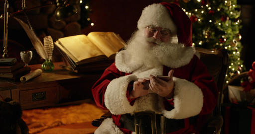 Santa Claus puts on his glasses, then fiddles with his smartphone Footage