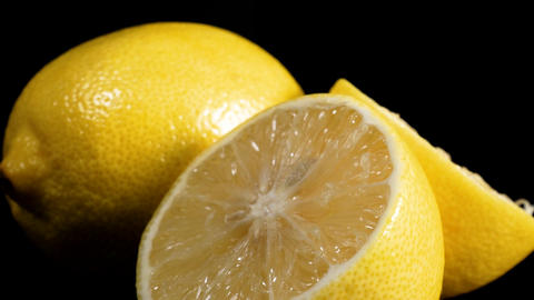 Fresh lemon slices rotate against black background Footage