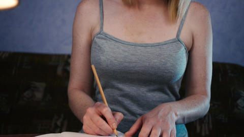 Young woman sitting at the table and thinks and writes Image