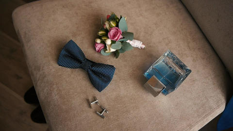elegant men's accessory for wedding, toilet water with buttonhole lie on a chair Footage