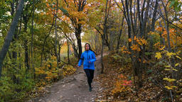 Woman in blue running jacket training in autumn colored forest Footage
