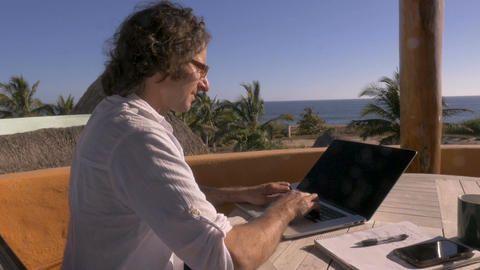 Handsome man telecommuting on laptop computer working at his home office ビデオ