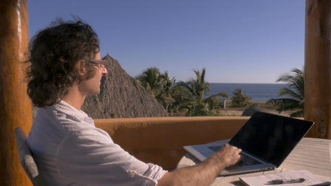 Man taking short break and enjoying the ocean view while working at his home Footage
