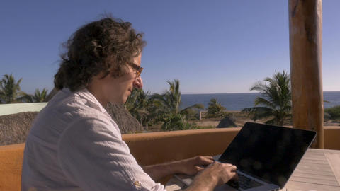Push out of man using laptop computer at home office telecommuting overlooking ビデオ