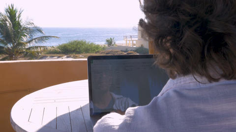 Handsome man working on spreadsheet on laptop computer at home with ocean view ビデオ