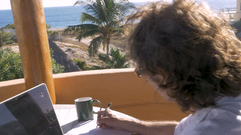 Man writing with pen and paper while working on laptop computer with charts and ビデオ