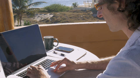 Handsome self employed entrepreneur man working on laptop from home office beach Footage