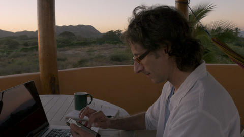 Attractive man scrolling through smart phone at home office by ocean looking at ビデオ