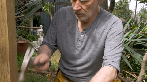 Handsome active retired senior man in 70s hammering a nail working on a home Footage