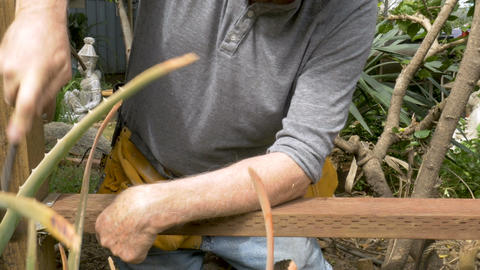 Active attractive senior man hammering a piece of wood into a metal brace during Footage