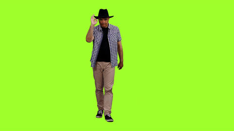 Adult man in plaid shirt and black cowboy hat walks on green background Footage