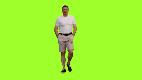 A man in white t-shirt walks with hands in pockets on green background Footage