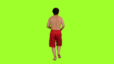 Back view of a shirtless male in red shorts jogging barefoot on green background Image