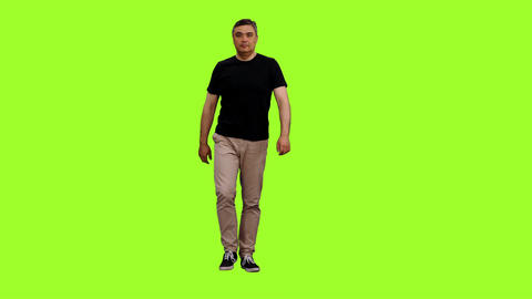 Front view of adult man in black t-shirt walks on green screen background Footage