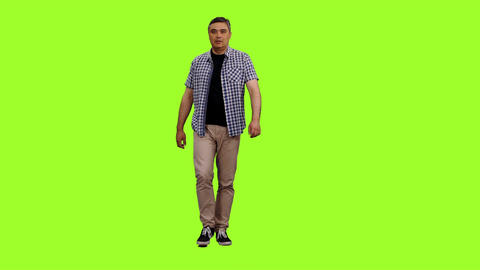 Front view of adult male in plaid shirt walks on green screen background Footage