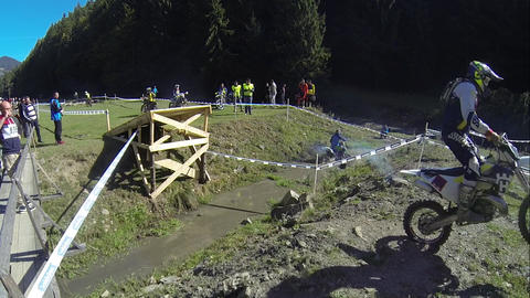 Motorcyclists jumping on a wooden trampoline during a motocross contest 01 Live Action