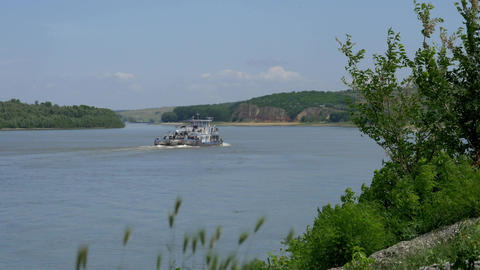 Tugboat sailing upstream on a large river guarded by low hills 63 Footage