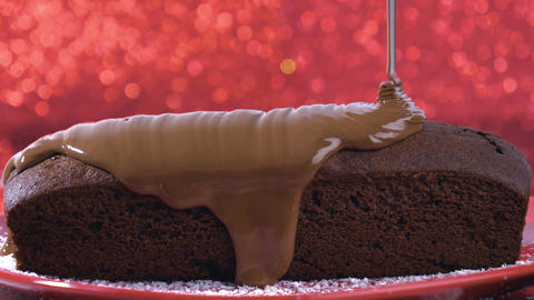 Melted chocolate flowing on chocolate cake on red background Footage