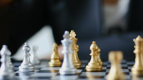 Close up shot hands of man and business woman moving gold chess and silver chess Footage