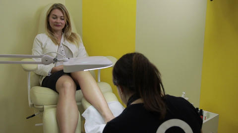Woman receiving pedicure in nail salon Live Action