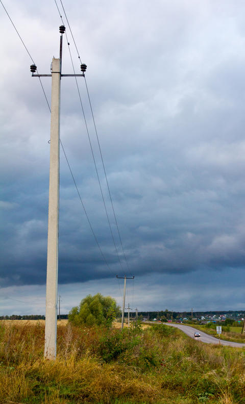 poles with electric wires in the evening autumn field Photo