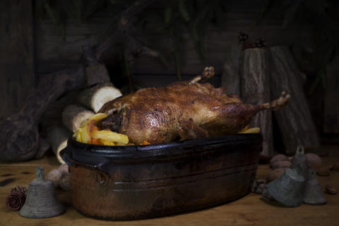Christmas Duck Roast At The Wooden Table With Wood Logs and Pine Branches In The Photo