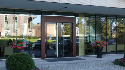 Modern office or residential building doorway reflecting street Footage