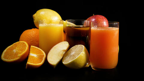 Fresh organic mixed juices and fruits rotating against black background Footage