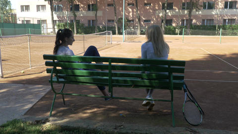 Girls sitting and resting on a bench on a tennis field after playing a match Footage