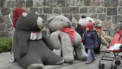 Little girl having fun with big teddy bears Footage