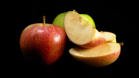 Organic green and red apple slizes rotates against black background Footage