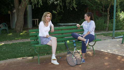 Two girls sitting on a bench chatting and resting with their tennis rackets near Footage