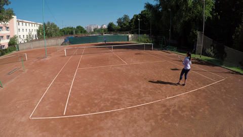 Two women play tennis outdoors at tennis arena Footage