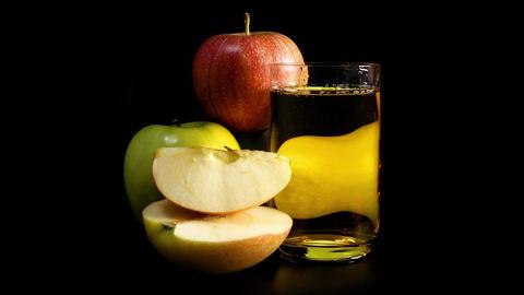 Fresh apple juice rotates against black background Footage