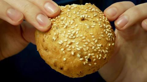 Woman hands break a crispy crust bun with sesame seeds Live Action
