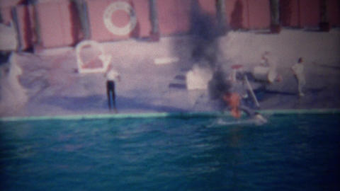 1955: Trained dolphin jumping thru flaming hoop of fire in pool Footage
