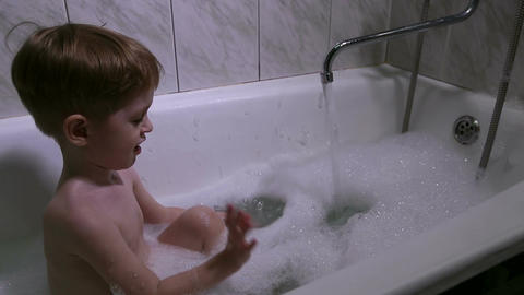 The little boy bathes in a bath with foam Footage