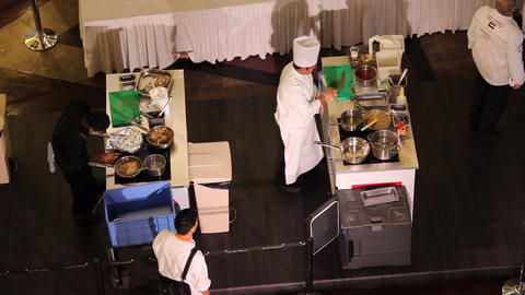 Two cooks make meals on separate tables, culinary competition, high angle view Footage