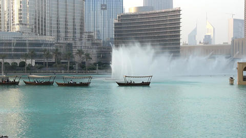 Water jet dance at lake, music fountain performance, boats with onlookers Live Action