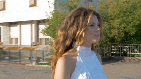 A beautiful woman in white clothes is walking along the street Filmmaterial