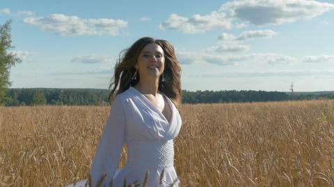 A singer in a white dress is singing on a field with wheat Footage