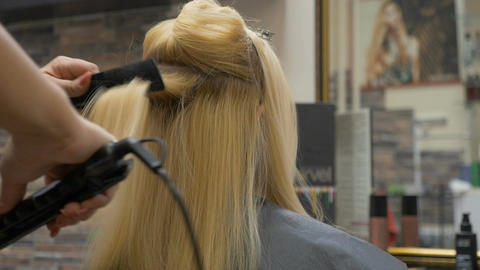 The stylist makes a hairstyle for a blonde woman Footage